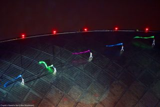 5 aerial performers run along the roof of Glasgow's Iconic Science Centre, lit in green, purple and blue.