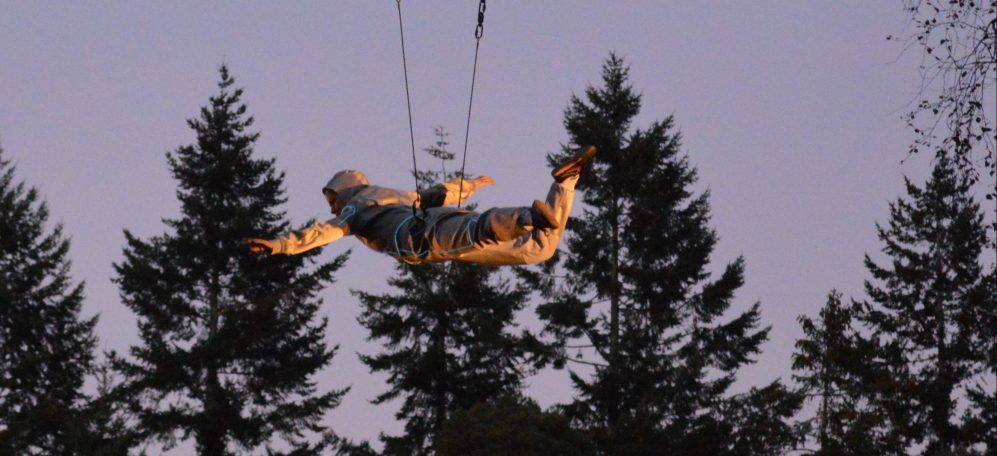 A performer flies across the trees suspended from a zip line