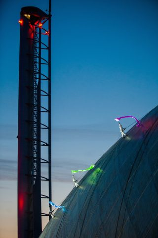Three performers walk along the roof of Glasgow's iconic Science centre brightly lit, each in a different colour; green, purple and blue
