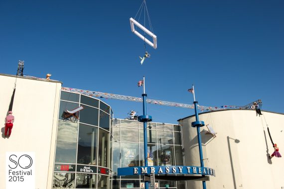 A performer flies from a wire suspended from a crane (out of shot) holding her leg and arm out. She is flying over a theatre. On either side of the theatre is a performer suspended from the roof waiking on the wall. It's a beautiful day.