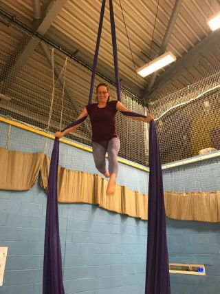 a women up high on an aerial fabric