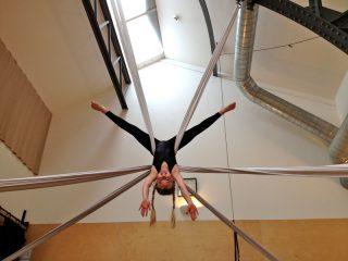 girl suspended in 2 silks, upside down star shape