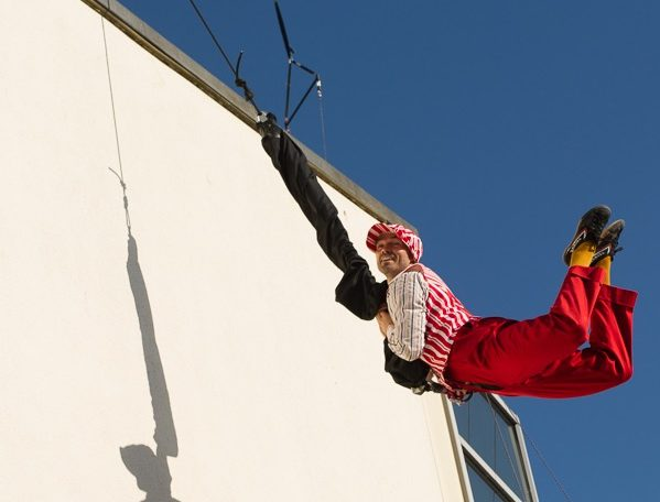 A performer swinging on a rope beside a wall