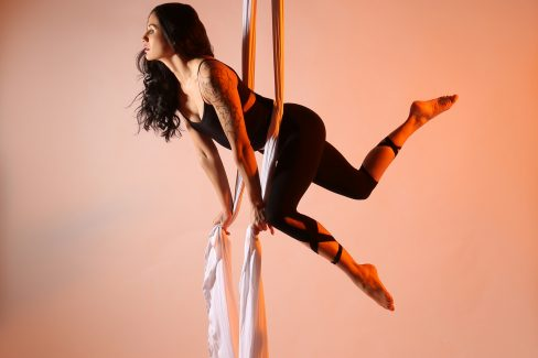 A woman is suspended on a set of white aerial silks, facing the left and kicking her legs behind her to the right. This is the tutor for the class, Ritti