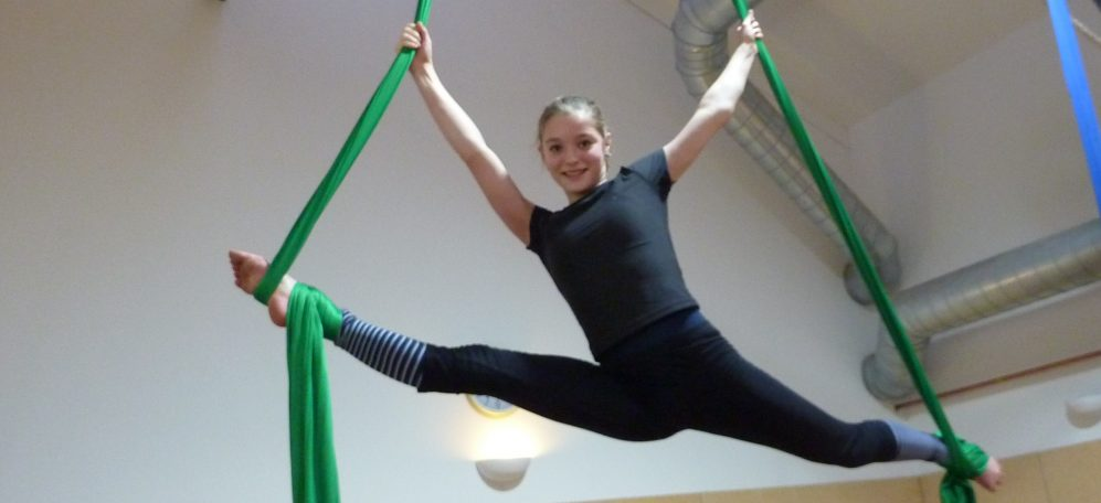 Female Youth in the air on a green aerial silk doing the splits