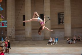 An image of a woman suspended on a trapeze outside to show off aerial arts