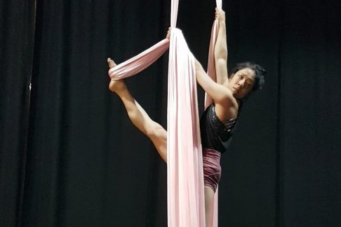a woman with dark hair and black top, suspended between 2 strands of aerial silk. The background is black and she is looking to camera