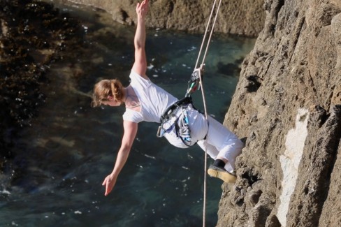 A woman is hanging in a harness on the side of a cliff, stretching out to the side, arms open wide, and back facing the camera. Demonstrating the kind of harness and moves for the workshop